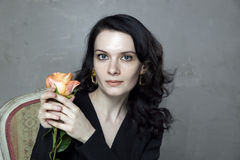 Portrait of attractive young brunette holding orange rose. Portrait of attractive caucasian young brunette holding orange rose Royalty Free Stock Photography