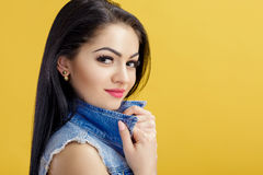 Portrait of attractive young brunette woman in denim vest on yellow background. Royalty Free Stock Photos