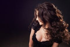 Portrait of attractive young brunette woman with luxurious curls. Beautiful curly-haired girl on dark background royalty free stock photos