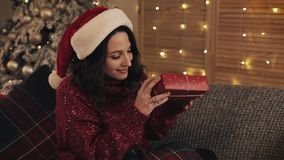 Portrait of attractive young brunette woman with wavy hair in santas hat sitting near Christmas tree at grey sofa stock video