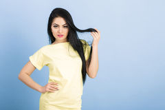 Portrait of  attractive young brunette woman in yellow dress on blue background. Stock Image