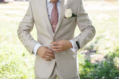 Portrait of an attractive young businessman or bridegroom in urban background wearing white suit. Man buttoning jacket Royalty Free Stock Images