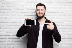 Portrait of attractive young businessman in casual clothes pointed a smart phone, looking in camera and smiling Stock Images