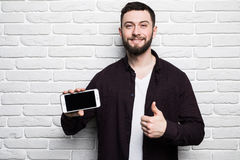 Portrait of attractive young businessman in casual clothes pointed a smart phone with thumbs up, looking in camera and smiling Stock Image