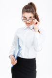 Portrait of attractive young businesswoman with folder looking over glasses. Over white background Royalty Free Stock Photography