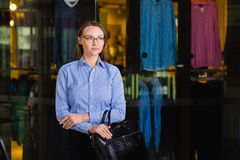 Portrait of a attractive Young Businesswoman Holding a briefcase. Standing near the shop with clothing and looking away Royalty Free Stock Photography