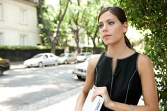 Business woman holding laptop. Portrait of an attractive young businesswoman holding a laptop computer under her arm while in a leafy street in the city with royalty free stock photo