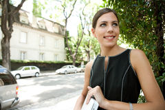 Business woman holding laptop. Portrait of an attractive young businesswoman holding a laptop computer under her arm while in a leafy street in the city with royalty free stock photos
