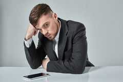 Portrait of attractive young caucasian man using cellular phone while sitting at office table. Royalty Free Stock Images