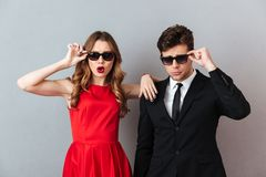 Portrait of a attractive young couple dressed in formal wear. And sunglasses posing while standing and looking at camera over gray wall background Royalty Free Stock Images