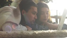Portrait of attractive young couple having fun spending the weekend together. Young guy and girl lying on the floor stock footage