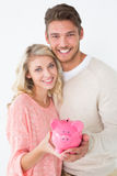 Portrait of attractive young couple holding piggybank Stock Photography