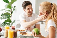 Portrait of an attractive young couple in love. Having tasty breakfast while sitting at the table in a kitchen Royalty Free Stock Photo