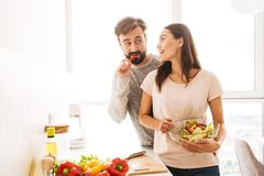Portrait of an attractive young couple in love. Cooking salad together while standing on a kitchen Royalty Free Stock Photography