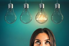 Idea and innovation concept. Portrait of attractive young european businesswoman with row of glowing glass lamps on blue background. Idea and innovation concept stock image