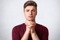 Portrait of attractive young European male keeps palms pressed, has pleading expression, asks for good fortune, prays indoor, pose. S against white concrete wall Stock Images
