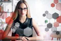 Job and website concept. Portrait of attractive young european woman with glasses sitting in modern office with abstract hexagonal pattern. Job and website royalty free stock image