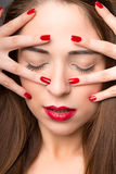 Portrait of attractive young female, eyes closed, with red nail polish, on dar Stock Photography
