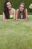 Portrait of attractive young female friends relaxing in park Royalty Free Stock Image