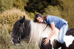 Portrait of attractive young female rider embracin. G her horse and looking at camera Stock Photos