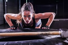 Attractive fit woman posing on tire with sledgehammer in fitness gym stock photos