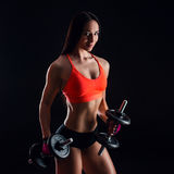 Portrait of an attractive young fitness woman in sportswear doing workout with dumbbells on black background. Royalty Free Stock Image