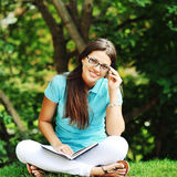 Portrait of attractive young girl with book in a park Royalty Free Stock Photos