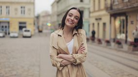 Portrait of Attractive Young Girl Wearing Beige Trench Smiling and Laughing Standing with Crossed Hands at City. Background stock footage
