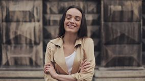 Portrait of Attractive Young Girl Wearing Beige Trench Smiling and Laughing Standing with Crossed Hands Close Up. Portrait of Attractive Young Girl Wearing stock footage