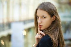 Portrait of attractive young haired woman with finger on lips. Portrait of attractive girl with finger on lips, concept of student show quiet, silence, secret Stock Photography