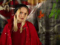 Portrait of an attractive young hipster girl in a knitted hat against the wall with inscriptions stock photography