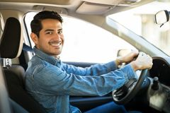 Attractive man driving a car. Portrait of attractive young hispanic man sitting in the driving seat of his car and making an eye contact stock image