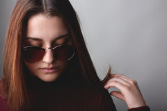 Portrait of attractive young lady with long brown hair wearing sunglasses and red sweater looking down with sad expression thinkin. G about something. Stylish Royalty Free Stock Image