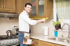 Latin handyman taking measurments. Portrait of an attractive young Latin handyman taking some measurements in a kitchen cabinet Royalty Free Stock Images