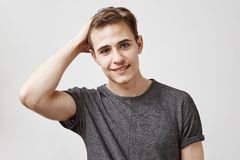 Portrait of an attractive young man in a gray shirt touching his hair. He asks classmate to give him copy her project. Portrait of an attractive young man in a royalty free stock photography