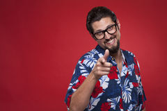 Portrait of a attractive young man in Hawaiian outfit pointing a Royalty Free Stock Images