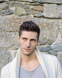 Portrait of attractive young man outdoors against stone wall Stock Photo
