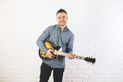 Man playing guitar. Portrait of attractive young man playing guitar on white brick wall background. Music, rock, leisure, hobby concept Royalty Free Stock Image