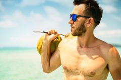 Portrait of an attractive young man on a tropical beach. Muscular young athletic man lying on the beach with a naked torso in underwear. Young handsome man in Stock Image
