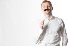 Portrait of an attractive young man wearing a retro style fake mustache.  royalty free stock images
