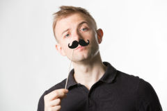 Portrait of an attractive young man wearing a retro style fake mustache. Stock Image