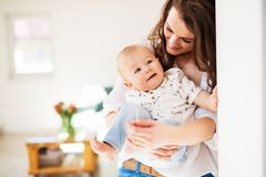 Portrait of a young mother with a baby son at home. Copy space. royalty free stock photos