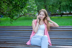 Portrait of an attractive young professional woman using a smartphone while sitting on a wooden bench in a park, smiling stock photo