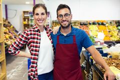 Attractive young sellers looking at camera in health grocery shop stock photography