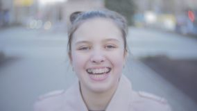 Portrait of an attractive young teen girl looking at the camera and smiling. Close shot stock video