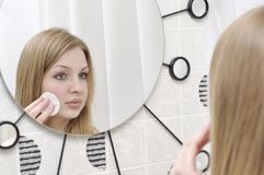 Portrait of attractive young woman. Who looks though mirror in bathroom and cleans her cheek royalty free stock images