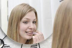 Portrait of attractive young woman. Who looks though mirror in bathroom and does make up stock photo