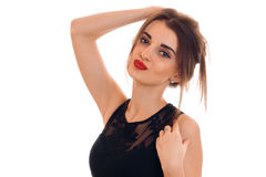 Portrait of an attractive young woman in a black dress and red lipstick that keeps hair and looks into the camera Stock Image