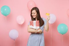 Portrait of attractive young woman in blue dress holding credit card and red box with gift present on pastel pink. Background with colorful air balloon royalty free stock photography