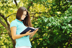 Portrait of attractive young woman with book in a green park Stock Photography